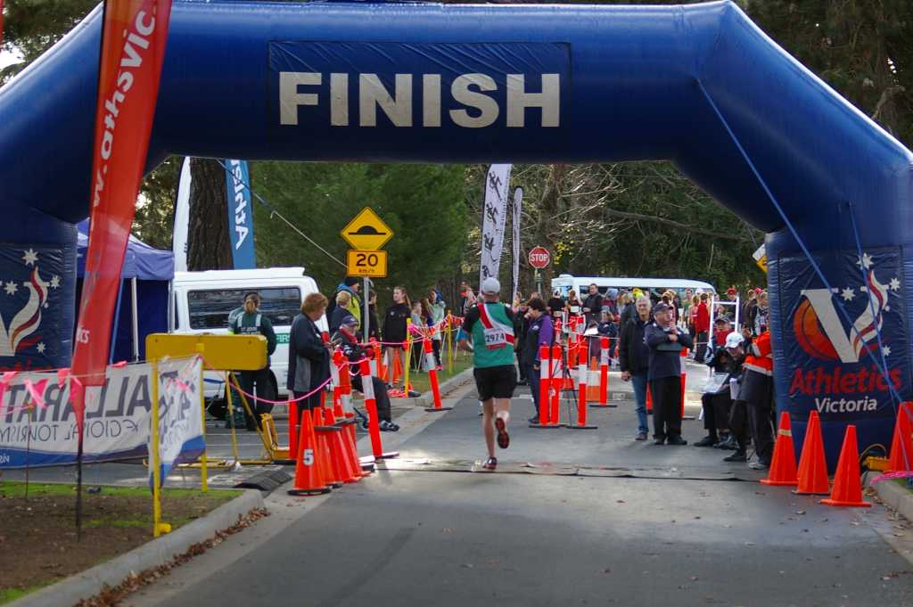 Travis crossing the finish line